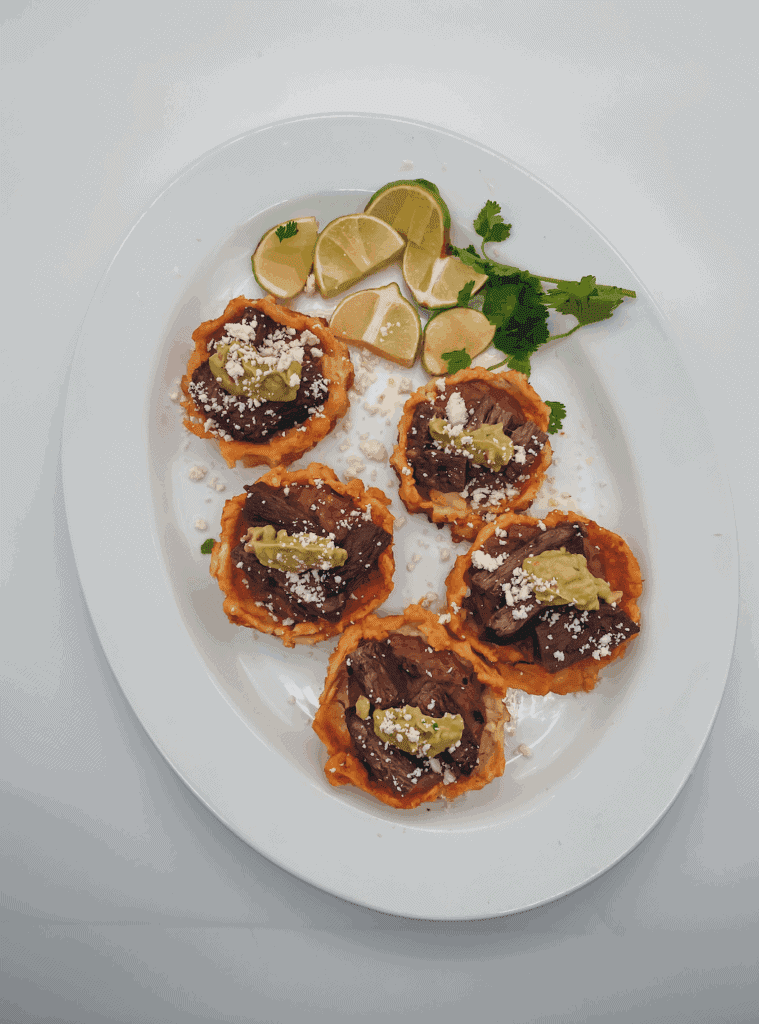 This Mexican Sopes with Carne Asada is made with carne asada, refried beans, maseca, guacamole and cotija cheese.