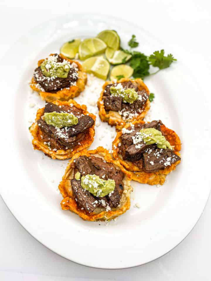 This Mexican Sopes recipe is made with carne asada, refried beans, maseca, guacamole and cotija cheese and cooked to perfection!