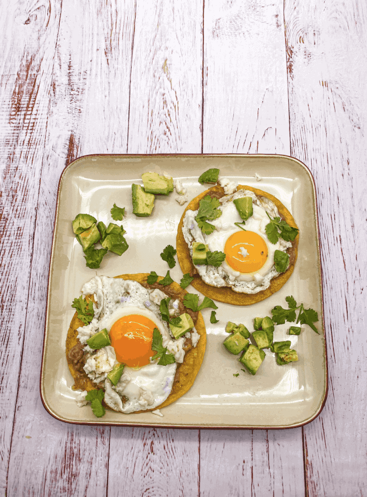 Huevos Rancheros is a fried tortilla topped with a Sunny-side egg and garnished with salsa verde, cilantro, avocado, cheese and sour cream.
