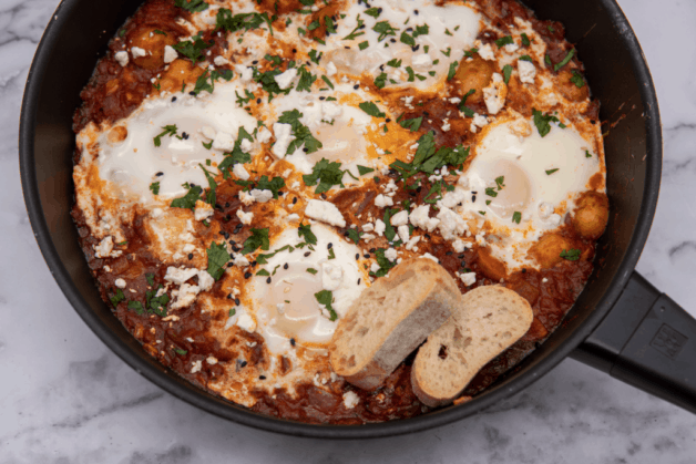 This Spicy Potato Shakshuka is made with spiced tomato sauce, harissa, poached eggs and garnished with cilantro and feta cheese!