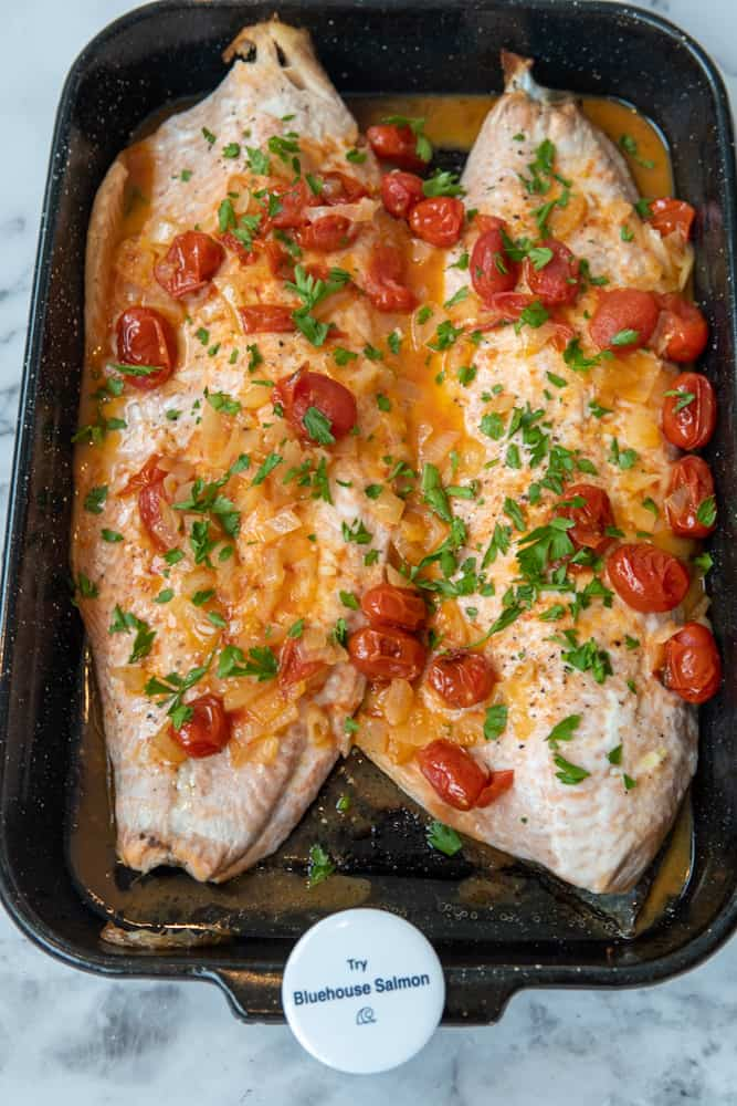 This White Wine Salmon with Blistered Tomatoes is made with salmon, white wine, cherry tomatoes, onion, garlic and garnished with parsley.